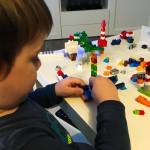 Liam bekommt sein erstes eigenes Legoset (mit kleinen Steinen) und baut begeistert drauf los.